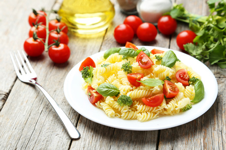Delicious pasta on plate on grey wooden background Stockfoto