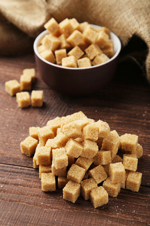 hyperglycemia: Brown sugar in bowl on brown wooden background