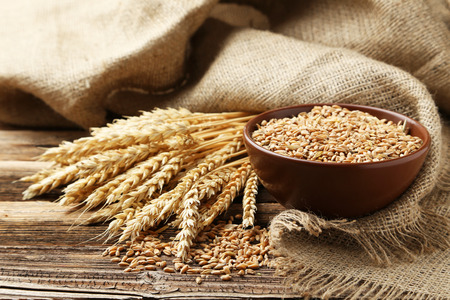 Ears of wheat and bowl of wheat grains on brown wooden background