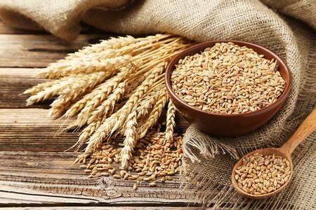 Weizenähren und Schüssel Weizenkörner auf braunen hölzernen Hintergrund Standard-Bild - 41910579