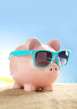 holiday profits: Piggy bank with sunglasses on the beach