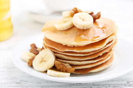 Tasty pancakes with banana and walnut on white wooden background Foto de archivo