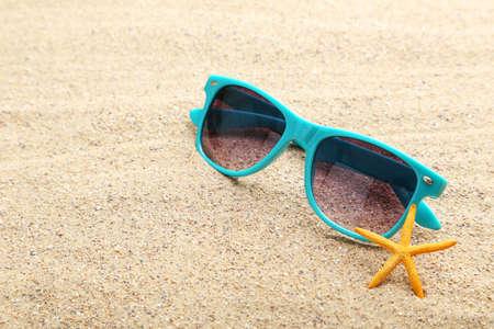 anteojos: Estrellas de mar con gafas en una playa de arena