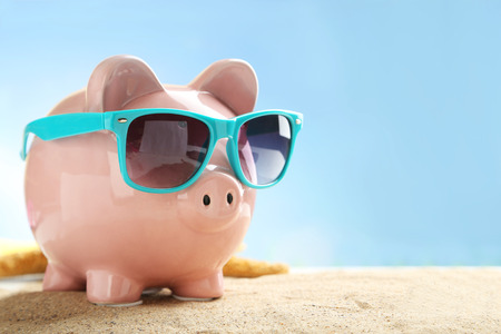 Spaarvarken met een zonnebril op het strand Stockfoto