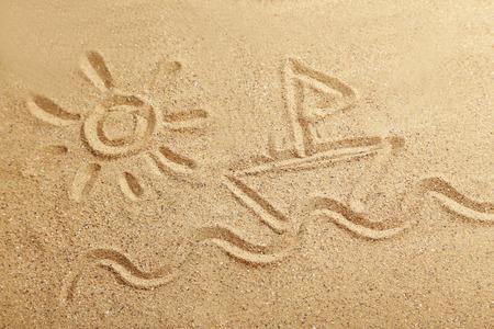 sand drawing: Drawing sun and ship on beach sand