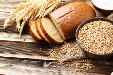 wheat: Ears of wheat and bowl of wheat grains on brown wooden background