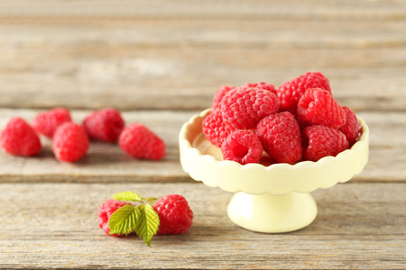 cake stand: Red raspberries on cake stand on grey wooden background