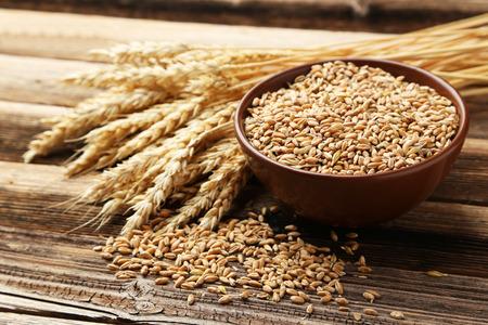小麦と茶色の木製の背景上の小麦粒のボウルの耳