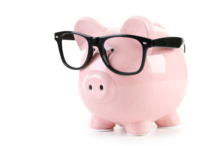Pink piggy bank with glasses isolated on a white 스톡 콘텐츠