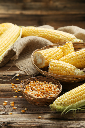 Corns in basket on a brown wooden background