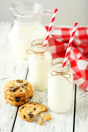dairying: Two bottles of milk with striped straws and cookies on white wooden background