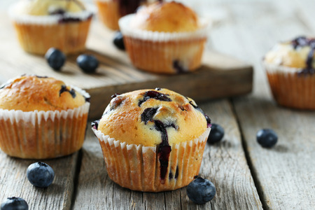 Tasty blueberry muffins on a grey wooden background 스톡 콘텐츠