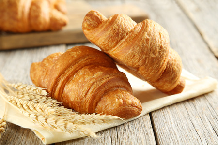 Tasty croissants with spikelets on grey wooden background