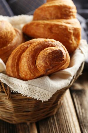 croissant: Tasty croissants in basket on brown wooden background