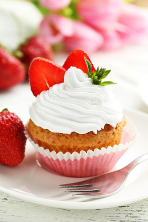 white cream: Tasty cupcake with fresh strawberry on white wooden background Stock Photo