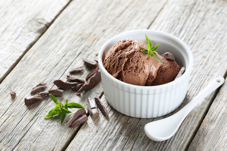Sweet chocolate ice cream in bowl on grey wooden background