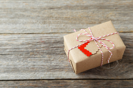 gift parcel: Beautiful gift box on grey wooden background Stock Photo