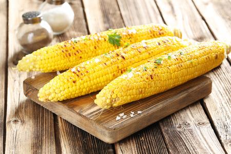 Lekkere verse gegrilde maïs met boter op bruine tafel en snijplank Stockfoto