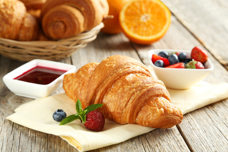 croissant: Fresh tasty croissants with berries on grey wooden background