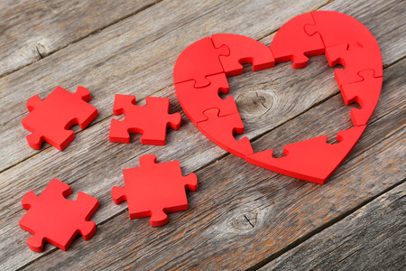 amorousness: Red puzzle heart on grey wooden background