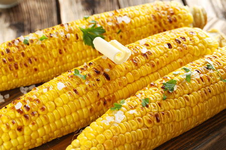 Fresh tasty grilled corn with butter on brown table