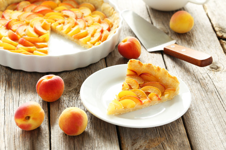 cake plate: Slice of apricot pie on grey wooden background Stock Photo