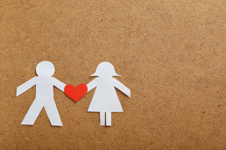 Paper people together in love on the brown background