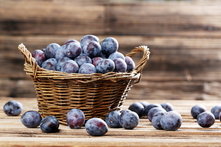 Fresh plums in basket on brown wooden background