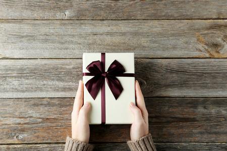 Vrouwelijke handen die gift box op grijze houten achtergrond