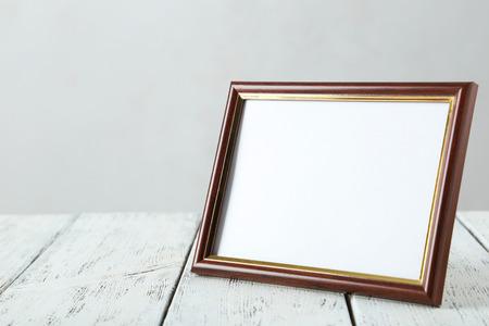 Wooden frame on white wooden background