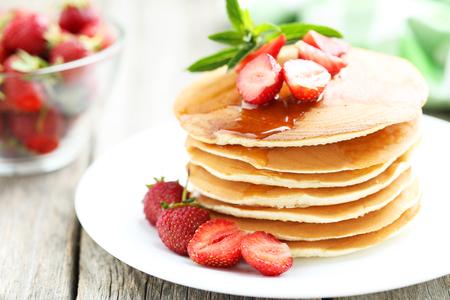 Geschmackvolle Pfannkuchen mit Erdbeeren auf grau Holzuntergrund Standard-Bild - 44845325