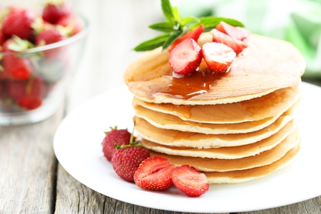 Tasty pancakes with strawberry on grey wooden background Фото со стока