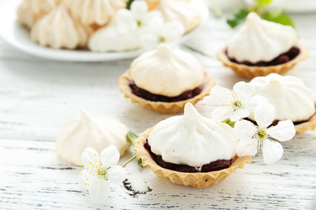 French meringue cookies in tartlet on white wooden background Stock Photo