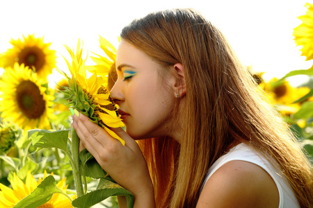 Beatiful girl in the sunflowers field