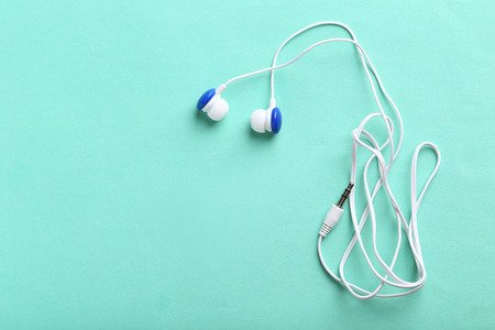 garniture: White headphones on a mint paper background