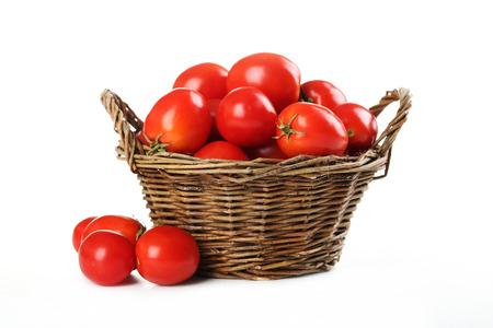 jitomates: Tomates rojos frescos en la cesta aislados en blanco Foto de archivo