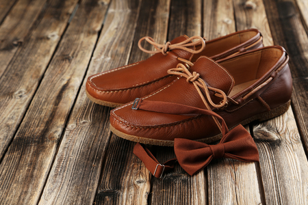 moccasins: Fashion brown shoes with bow tie on a brown wooden table
