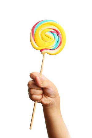 paleta de caramelo: dulce caramelo con palo explotaci�n de la mano del ni�o en el palillo