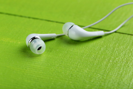 handsfree phone: White earphones on a green wooden table Stock Photo