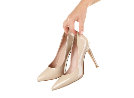 Female hand holding beige high-heeled shoes on white background Stock Photo