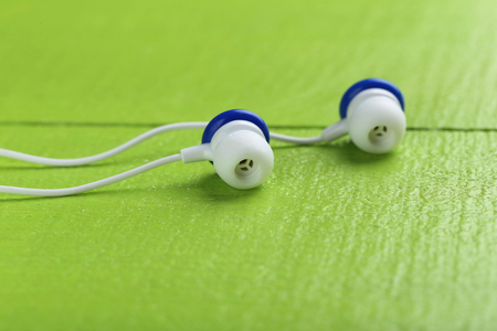 handsfree telephone: White earphones on a green wooden table Stock Photo