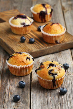 Tasty blueberry muffins on a grey wooden background Archivio Fotografico