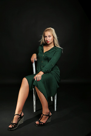 Young beautiful girl in green dress sitting on a chair on black background Stock Photo