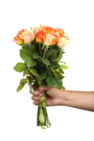 Male hand holding bouquet of orange roses on white background Stock Photo