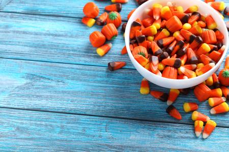 maiz: Pastillas de caramelo de Halloween en un taz�n en el fondo de madera azul