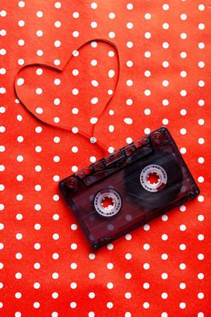 analogical: Audio tape cassette on red paper background Stock Photo