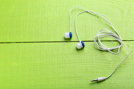handsfree phone: White headphones on a green wooden table