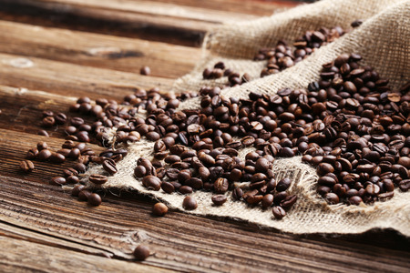frijol: Asado granos de caf� sobre un fondo de madera marr�n