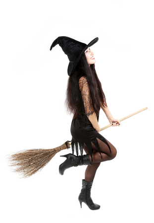broom: Young brunette witch with broom isolated on a white Stock Photo