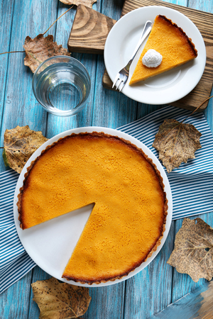 pumpkin leaves: Tasty pumpkin pie on plate on a blue wooden table Stock Photo